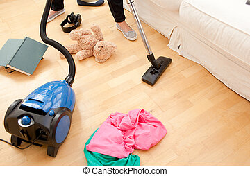 Close-up of a woman vacuuming the living-room