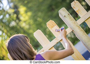 Woman varnishing a new wooden fence