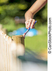 Woman varnishing a wooden fence outdoors in a home patio