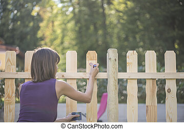 Woman varnishing a wooden picket fence