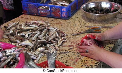 Woman Vendor Cut Up the Fish in the Fish Market. Slow Motion...