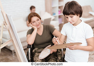 Woman veteran in wheelchair returned from army. Woman in a wheelchair watches her son paints on canvas.