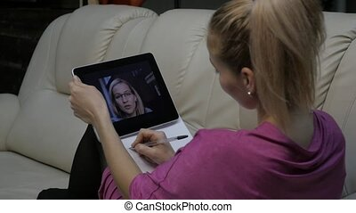 Woman video conferencing with tutor on laptop at home....