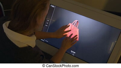 Woman Viewing 3D Model of a Bag on Big Touch Screen