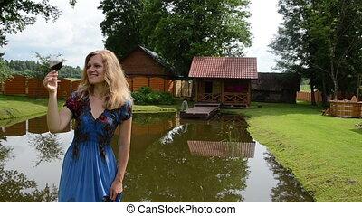 woman vine glass pond - Pretty woman in dress enjoy glass of...