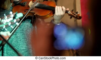 Woman violinist - musician playing the violin in night club,...