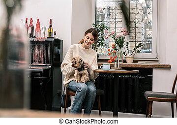 Woman visiting a dog-friendly cafe with her little friend
