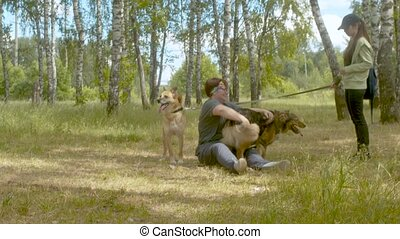 Woman volunteer sitting on the ground in the forest and caress the dog. Volunteering and helping concept.