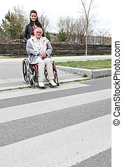 Woman waiting at a zebra crossing with an elderly lady in a wheelchair