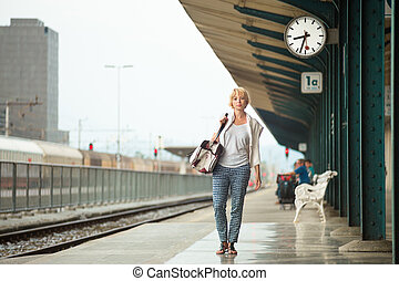 Woman waiting at platform of railway station bearing vintage shoulder bag.
