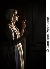 Woman waiting at the door in darkness