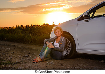 Woman waiting beside her car on a rural road