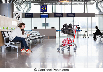 Woman waiting flight in airport lounge with luggage hand-cart