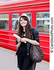 Woman waiting for a train with ticket in her hands