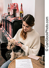 Woman waiting for her order in cafe with her dog
