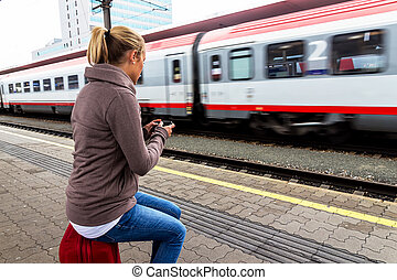 woman waiting for train and writes sms - a young woman ...