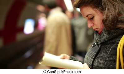 Woman waiting metro at station - Woman reading book while...