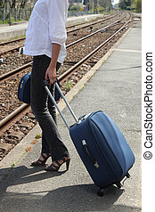 Woman waiting on a train platform with a suitcase