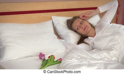 woman wake up and find tulip flowers. happy female smiling and looking at camera
