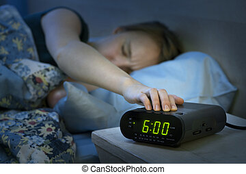 Woman waking up early with alarm clock - Young woman ...