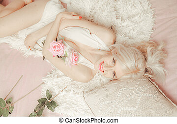 Woman waking up in The Morning. slender blonde female in her white bed.