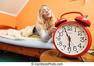 Woman waking up turning off alarm clock in morning