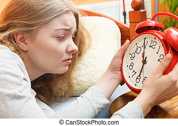 Woman waking up turning off alarm clock in morning - Unhappy...