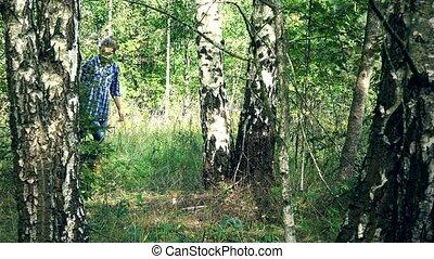 Woman walk and find red cap boletus mushroom under birch...