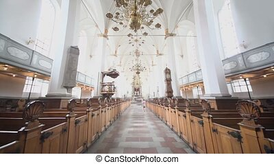 Woman walk in church with sanctuary and balcony for homily -...