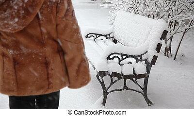 Woman walk in snow near bench in  park, wintertime