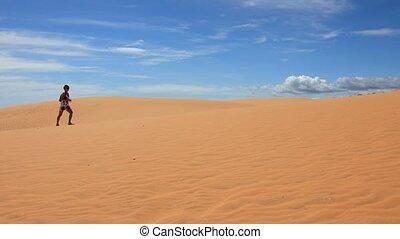 Woman walking across the sand dunes - Young woman walking...