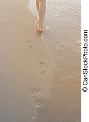 woman walking alone on sand beach leaving footprints in the sand