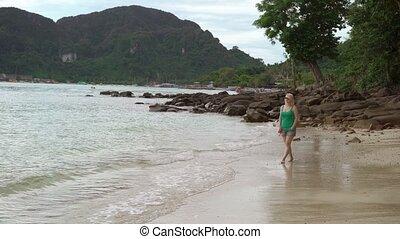 Woman walking alone on wild beach