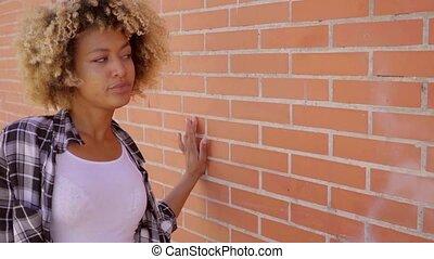 Woman Walking Along A Brick Wall.