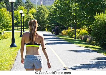 Woman walking along a jogging trail