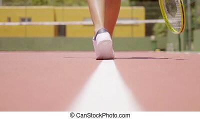 Woman walking along a line on a tennis court