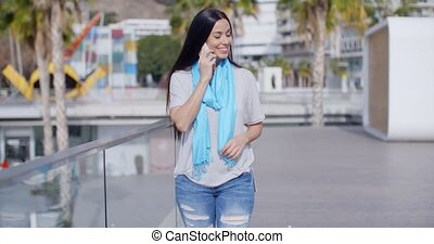 Woman walking along a promenade with a mobile