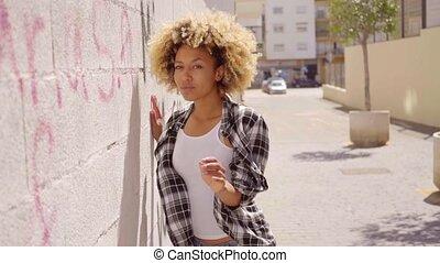 Woman Walking Along A Stone Wall.