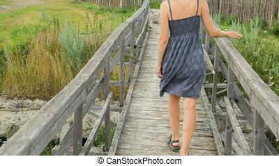 Woman walking along old wooden bridge