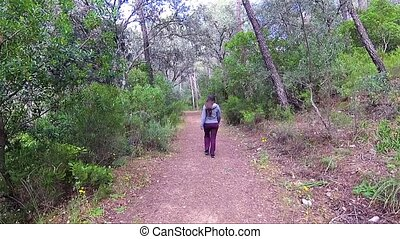 Woman walking along the path in the woods