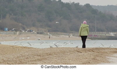 Woman walking along the sandy beach in autumn