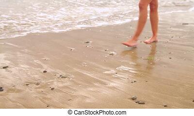 Woman walking along the tide on the beach