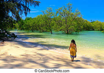 Woman walking along tropical beach