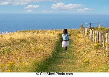 Woman walking along wild coastline