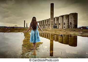 Woman walking among ruins