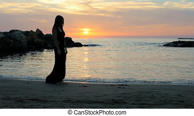 Beautiful woman dressed for night out crying on the beach during sunset