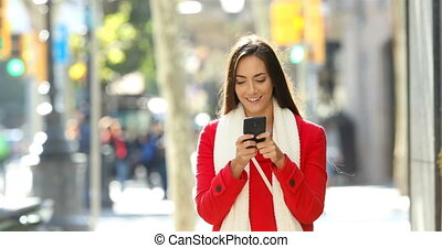 Woman walking and texting on phone in the street