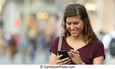 Woman walking and using a smart phone in the street