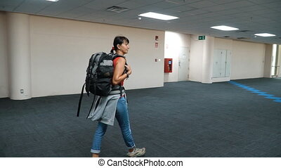 Woman walking at empty airport hallway