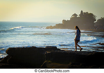 Woman walking at ocean coastline.